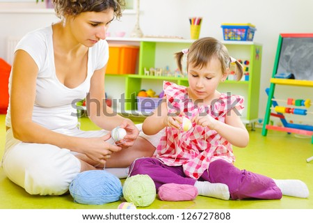 Young mother and little daughter decorating Easter eggs with colorful yarn strings