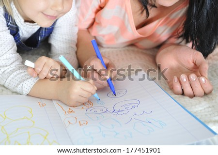 young Mother and little daughter lying and drawing together with markers having fun together