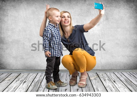 Young mother and little son are photographed on a mobile phone making selfie.Stylish,trendy,modern
