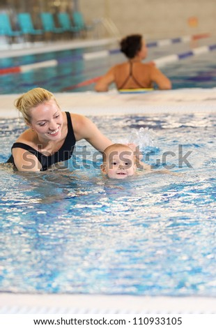 Young mother and little son in a swimming pool