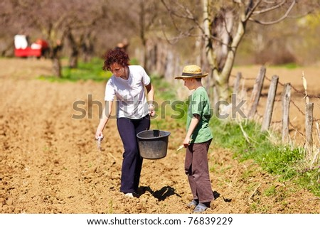 Young mother and son farmers planting seeds mixed with fertilizer