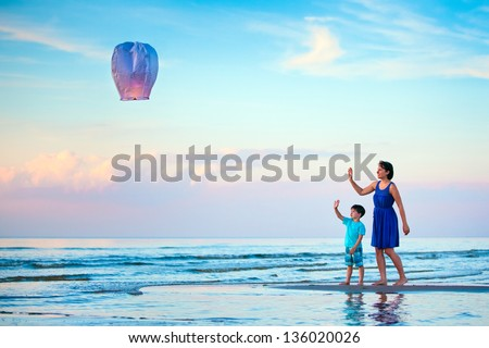 Young mother and son flying fire lantern together