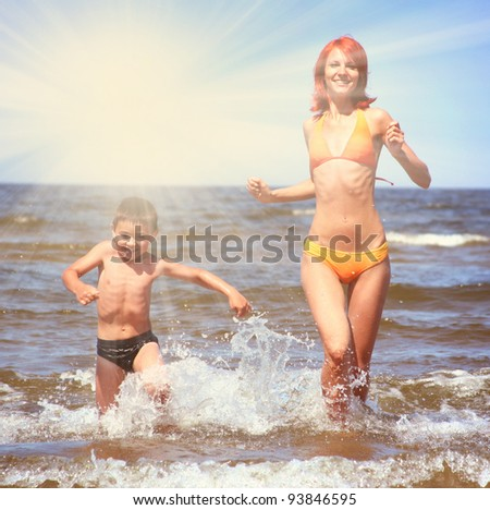 young mother and son having fun on the beach