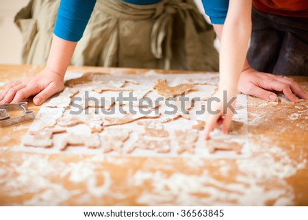 Young mother and son in kitchen making cookies