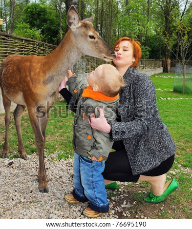 young mother and son pet  deer