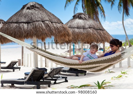 Young mother and son relaxing in a hammock on a caribbean beach