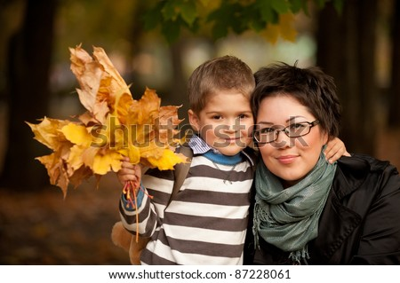 young mother and son together in autumn park with maple leaves