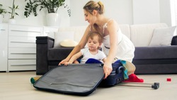 Young mother and toddler boy packing suitcase for holidays