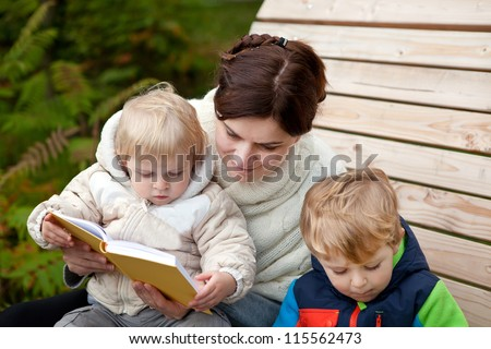 Young mother and toddler reading book in autumn park