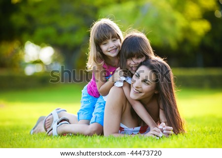 Young mother and two daughters playing in grass