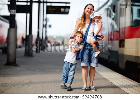 Young mother and two kids waiting for train on railway station platform