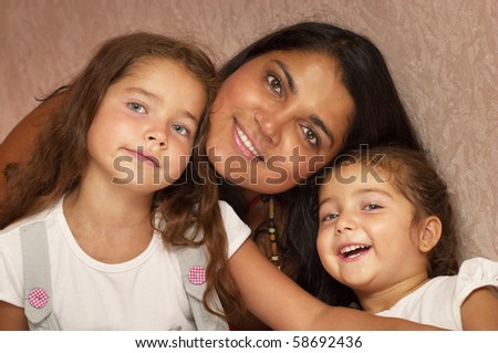 Young mother and two little sisters over defocused wallpaper background