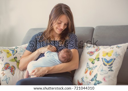 Young mother breastfeeding  her newborn baby boy at home