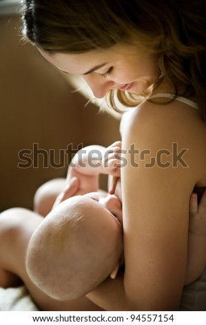 Young mother breastfeeding newborn baby