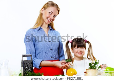 Young mother cooking fresh meal at home with her daoghter