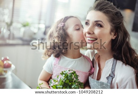 Young mother cooking with her little daughter #1049208212