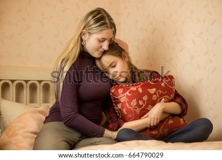 Young mother embracing and solacing teenage daughter