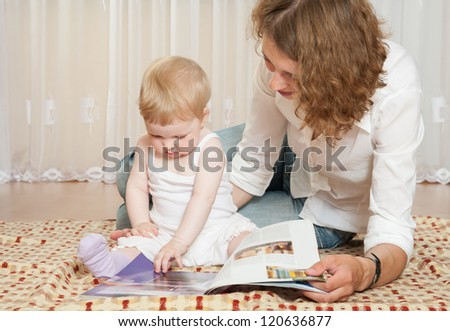 Young mother examining a magazine  with her little daughter at home