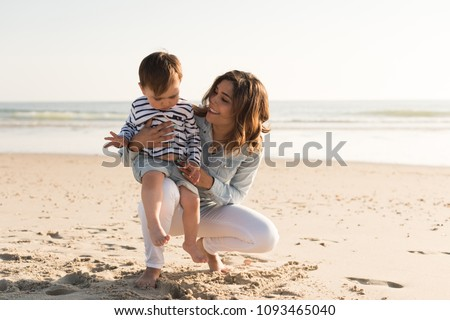 Young mother exploring the beach with her baby