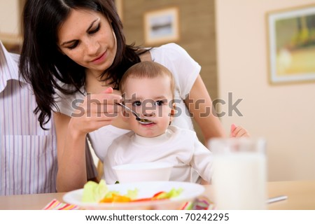 young mother feeding a baby at home in th e kitchen with a spoon