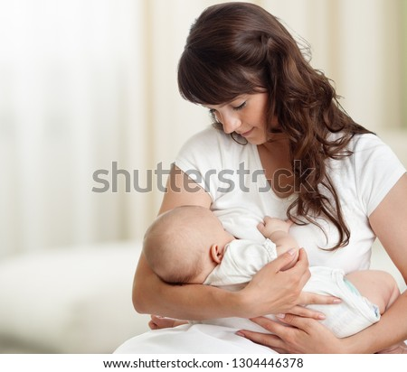 Young mother feeding breast her newborn baby at home in white room