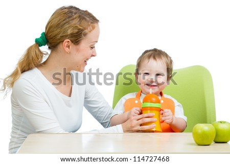 young mother feeding her baby boy isolated on white