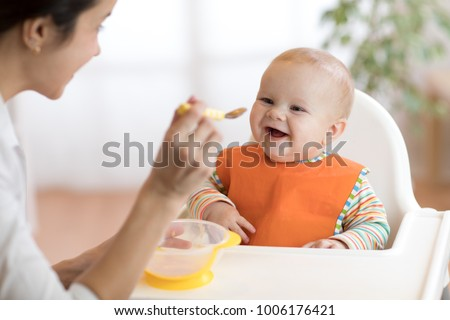 Young mother feeding her baby son with fruit puree