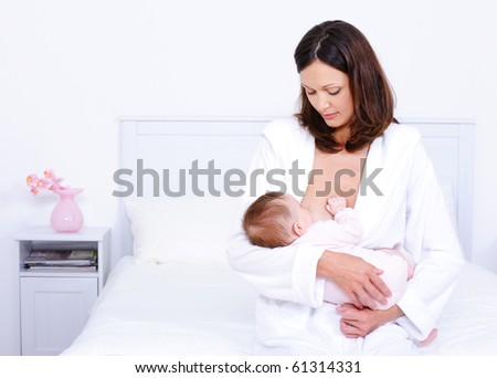 Young mother feeding her little baby with breast at home - indoors