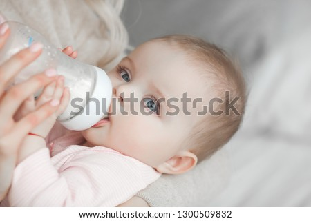 Young mother feeding her little cute baby daughter with bottle of child formula. Woman with her newborn baby at home. Mom taking care of a child. Alternative to breast feeding.