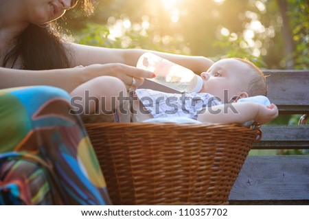 Young mother feeding her sun in the park