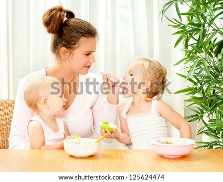 young mother feeding her two daughters from a spoon
