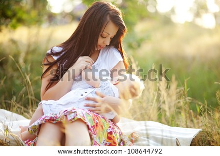 young mother feeding milk the infant baby outdoors