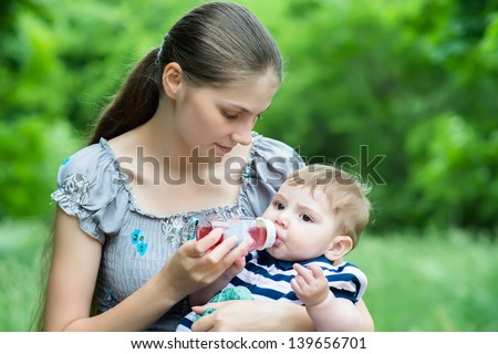 Young mother feeds her baby with milk from bottle