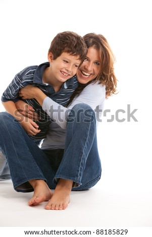 Young mother having fun tickling son isolated on a white background.