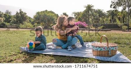 Young mother having fun with her two sons in a park - Love and family concept - Family having a pic nic - Focus on mother face Zdjęcia stock ©