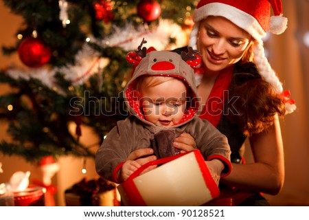 Young mother helping interested baby open present box at Christmas tree