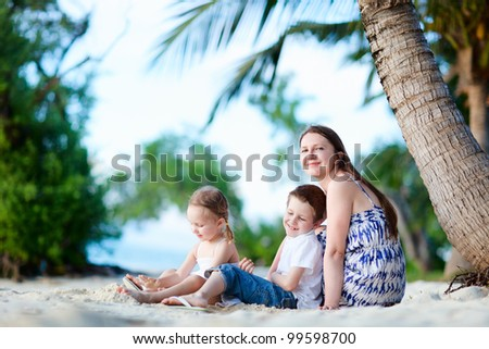 Young mother her two kids enjoying time at beach