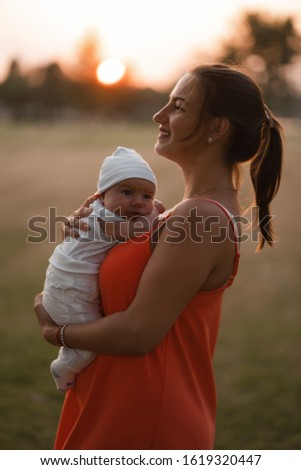 Young mother holding and playing with her baby boy child in city park standing wearing bright red dress - Son wears white cap - Family values warm color summer scene handheld