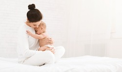 Young mother holding her newborn child, lulling baby in bed, copy space