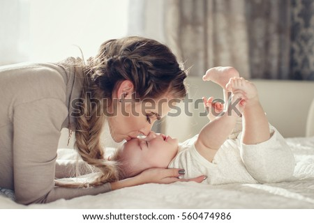 Young mother holding her newborn child. Mom nursing baby. Woman and new born boy relax. Nursery interior. Mother breast feeding baby. Family at home. Portrait of happy mother and baby #560474986