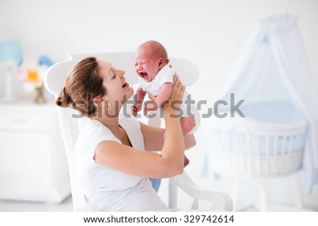 Young mother holding her newborn child. Mother comforting crying hungry baby. Woman and new born boy relax in a white bedroom with rocking chair and blue crib. Nursery interior. Family at home.