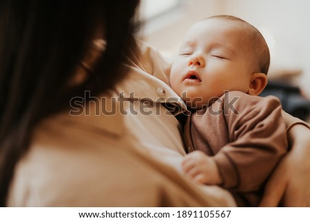 Young mother holding her newborn child. mother's care baby. Woman and new born girl relax. Baby sleeping on mom's arms Foto stock ©