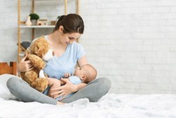 Young mother holding soft teddy bear playing with her newborn baby at home, free space
