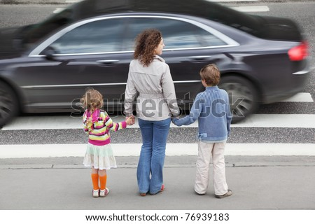 young mother holds hand of his little daughter and son and standing near cross road, behind, black car