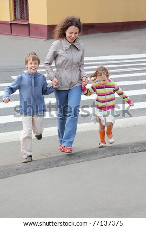 young mother holds hand of little daughter and son and crossing road, yellow house, focus on boy