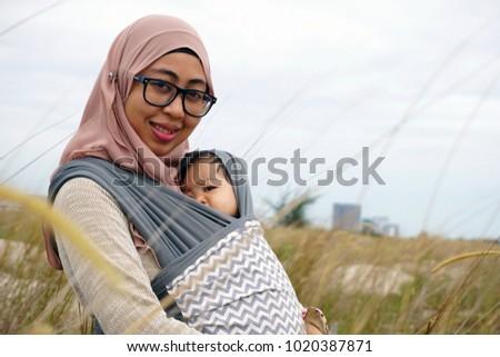 Young Mother hug her cute daughter outside a garden. Selective Focus. Motherhood Concept #1020387871