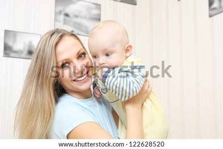 Young mother hugging baby  at home