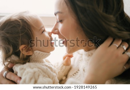Young mother hugging her little daughter, they sitting near window and smiling.  Stock photo ©