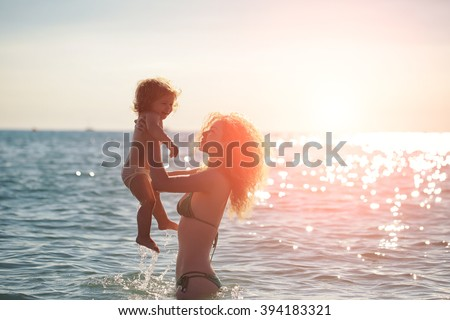 Young mother in bikini standing swimming and playing with male child boy in sea or ocean water sunny day outdoor on natural background, horizontal picture