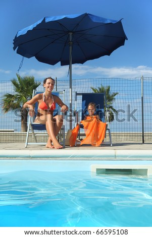 young mother in orange bikini and daughter sitting on beach chair near pool and smiling, palms